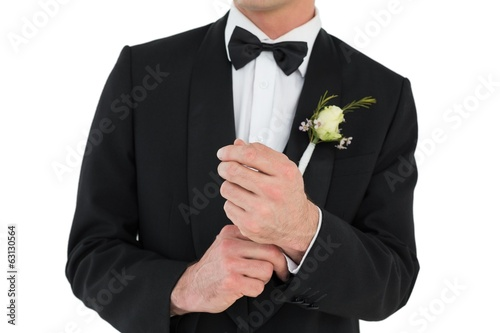 Mid section of groom adjusting cuff links