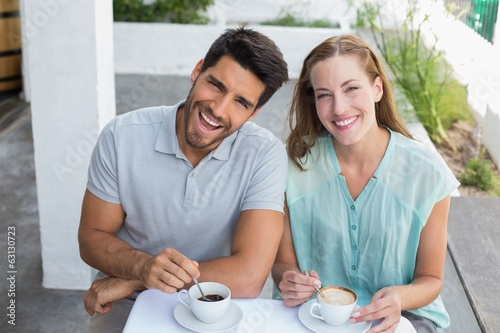 Happy young couple with coffee cups at café