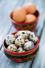 Wooden khokhloma tableware with raw quail and chicken eggs