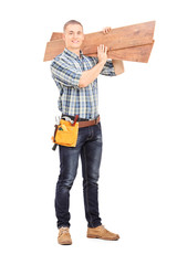 Male carpenter carrying planks over his shoulder