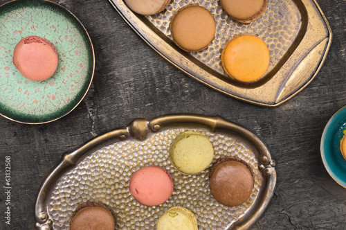 colorful macarons in colored metal bowls, wooden background