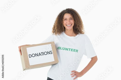 Smiling volunteer holding a box of donations with hand on hip