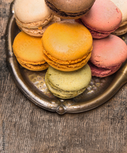 macarons on copper tray , old wooden background