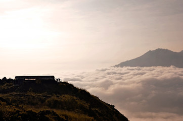 Above clouds with a mountain volcano view