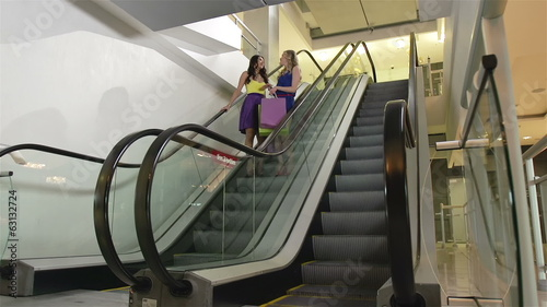 Ladies descending on escalator while doing shopping in the mall