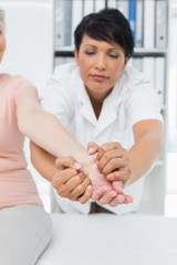 Physiotherapist examining a senior patients hand