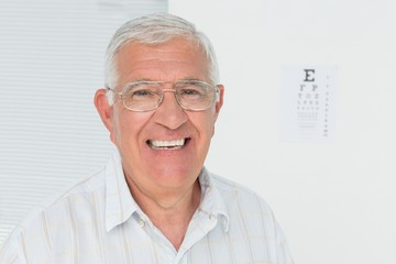 Portrait of a smiling senior man with eye chart in background