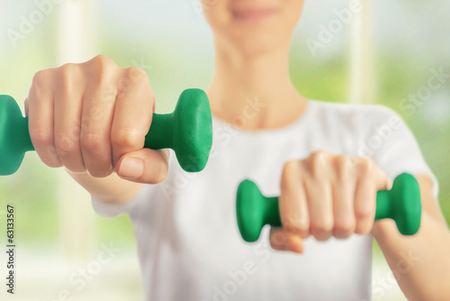 Fitness woman holds dumbbells