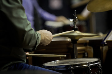 Hands of the man playing a drum set