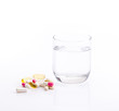 Drinking water and pills isolated on white