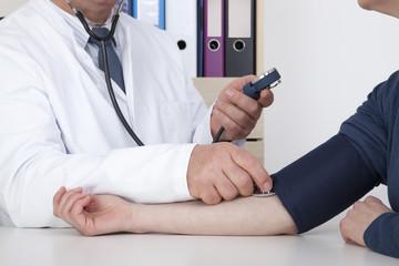 Experienced Doctor measures blood pressure