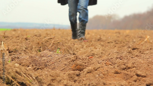 move across the field,man walking on the ground (dirt)