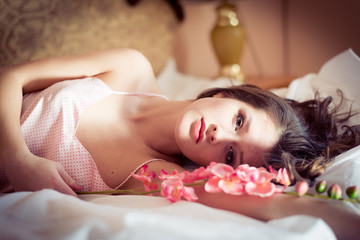 beautiful woman lying in bed with a flower orchid