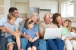 Multigeneration family using laptop in living room