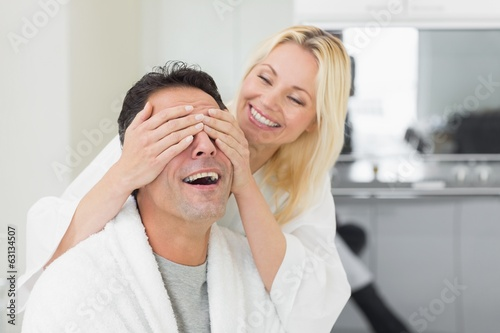 Smiling woman covering happy mans eyes in kitchen