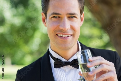 Young groom drinking champagne in garden
