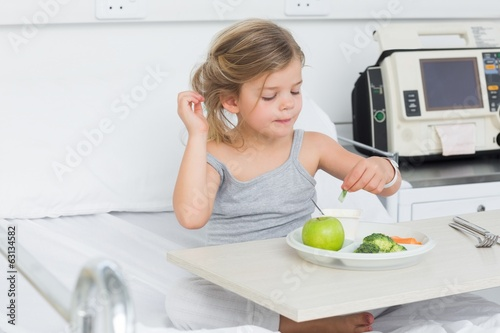 Girl eating healthy food in hospital bed