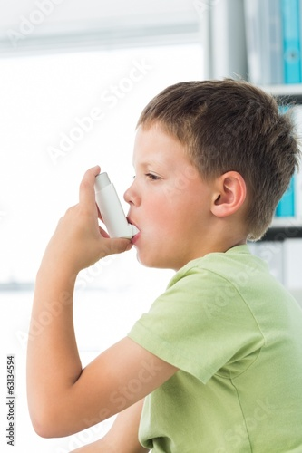 Boy using asthma inhaler in hospital