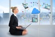 Blonde businesswoman sitting using laptop with cloud and app ico