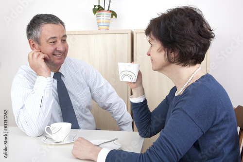 Man and woman chat over a cup of coffee
