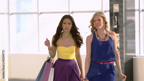 Two girlfriends chatting while walking in the mall