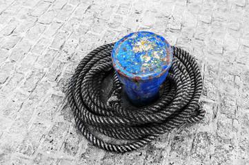 rusty bollard with ropes