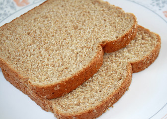 Two slices of fresh whole wheat bread on plate