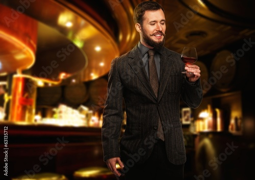 Handsome well-dressed man with glass of beverage