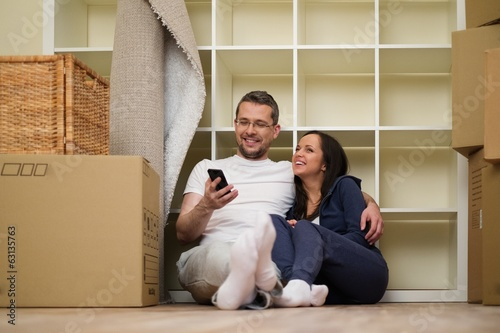 Young positive couple  among boxes in their new home