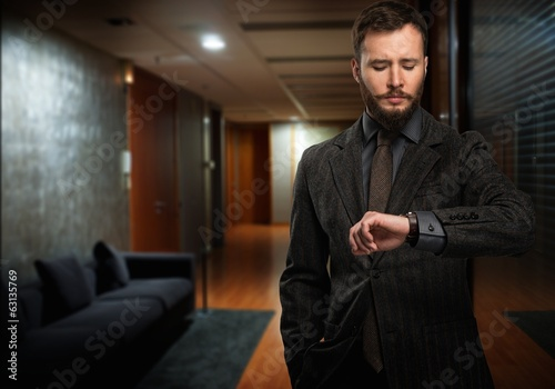 Handsome well-dressed man  looking at wrist watch