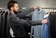 Handsome man with beard choosing shirt in a shop