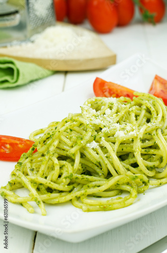 Italian pasta with pesto sauce on white plate