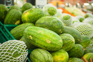 Bunch of watermelons on plastic boxes in store