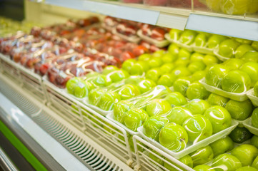 Rows of green and red apples in plastic package on shelf in stor