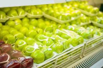 Rows of green apples in plastic package on shelf in store