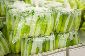 Plastic bags with bunch of cucumbers on shelf in store