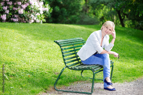 Handsome blond woman on bench looking at camera
