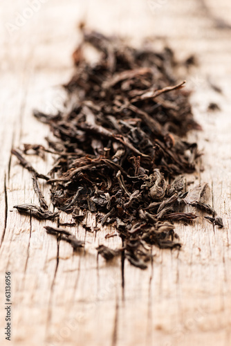 Black tea on wooden background macro