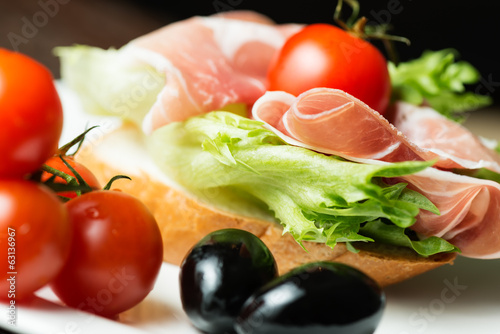 Ham sandwich with tomato and olive close up