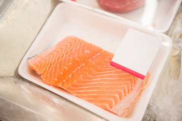 Plastic packed slice of salmon fish on shelf in supermarket