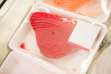 Plastic packed slice of tuna fish on shelf in supermarket