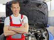 Master mechanic is proud of his job in a garage