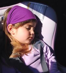 Bimba che dorme in auto