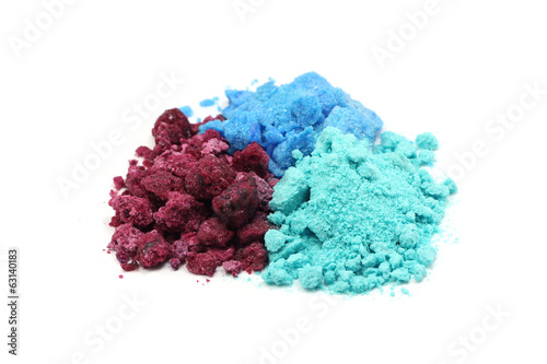 handful of red, blue and green salt on white background