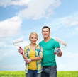 smiling couple in gloves with paint rollers