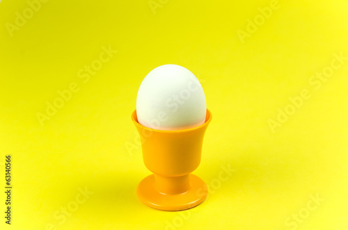 Egg in cup at yellow background