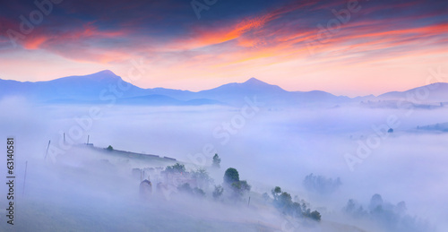 Silhouettes of the mountains and village in the morning mist.