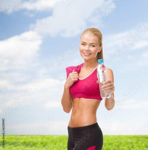 sporty woman with bottle of water and towel