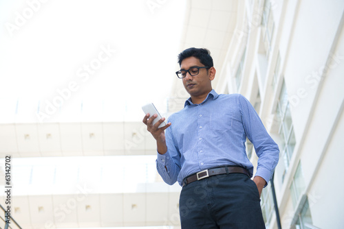 indian business male holding a phone