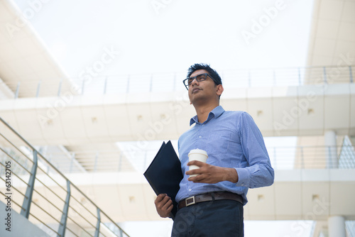 indian business male with coffee and folder